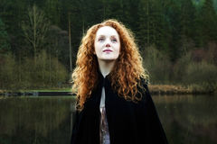 Beautiful Woman with long cascading red hair looking up. To the sky. Wearing a black cloak with a lake and forest background. Llyn Mymbyr Snowdonia Wales Royalty Free Stock Photography
