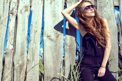 Beautiful woman with long chestnut hair wearing jumpsuit and trendy aviator sunglasses at the wooden fence royalty free stock photos