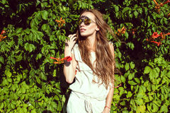 Beautiful woman with long chestnut hair wearing trendy round mirrored sunglasses standing at the Virginia creeper hedge stock images