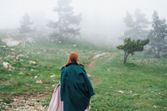 Beautiful woman in a long coat and in a dress walking through the mountains in the fog.  Stock Image