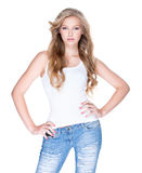 Beautiful woman with long curly hair in blue jeans. Beautiful young sexy woman with long curly hair in blue jeans posing in studio over white background Royalty Free Stock Images