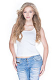 Beautiful woman with long curly hair in blue jeans. Beautiful young sexy woman with long curly hair in blue jeans posing in studio over white background Royalty Free Stock Photography