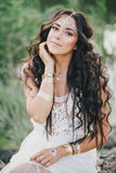 Beautiful woman with long curly hair dressed in boho style dress posing near lake Stock Photos