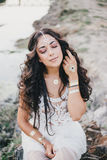 Beautiful woman with long curly hair dressed in boho style dress posing near lake Stock Photography