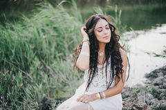 Beautiful woman with long curly hair dressed in boho style dress posing near lake. Beautiful young woman with long curly hair dressed in boho style dress posing stock images
