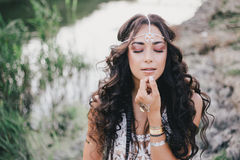 Beautiful woman with long curly hair dressed in boho style dress posing near lake Royalty Free Stock Photos
