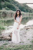 Beautiful woman with long curly hair dressed in boho style dress posing near lake Stock Image