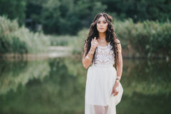 Beautiful woman with long curly hair dressed in boho style dress posing near lake Royalty Free Stock Photography