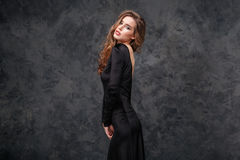 Beautiful woman with long curly hair in evening black dress. Tempting beautiful young woman with long curly hair in evening black dress over grey background stock photos