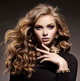 Beautiful woman with long curly hair and gold jewelry. Posing at studio royalty free stock photo