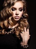 Beautiful woman with long curly hair and gold jewelry. Posing at studio royalty free stock images