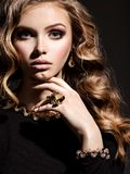 Beautiful woman with long curly hair and gold jewelry. Posing at studio royalty free stock photography