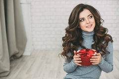 Beautiful woman with long curly hair holding gift box heart and looking at the camera. Royalty Free Stock Images