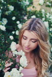 Beautiful woman with long curly hair smells white roses outdoors, closeup portrait of sensual girl face Stock Photos