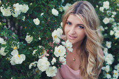 Beautiful woman with long curly hair smells white roses outdoors, closeup portrait of sensual girl face. Blonde female portrait with flowers, elegant lady in Stock Photo