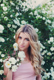 Beautiful woman with long curly hair smells white roses outdoors, closeup portrait of sensual girl face Royalty Free Stock Photo