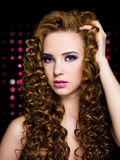 Beautiful woman with long curly hairs. Portrait of young woman with long curly hair. Blinking Background. Bokeh royalty free stock images