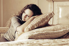 Beautiful woman with long curly hairs in a bedroom Stock Images