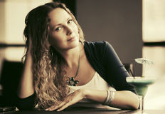 Beautiful woman with long curly hairs at restaurant Royalty Free Stock Photography