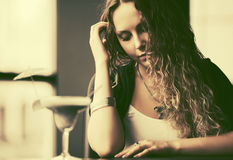 Beautiful woman with long curly hairs at restaurant Royalty Free Stock Photo