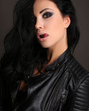 Beautiful woman with long dark hair and bright makeup, wears black leather jacket Royalty Free Stock Photography