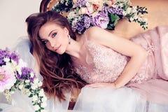 Beautiful woman with long dark hair in elegant dress posing among flowers Royalty Free Stock Photos