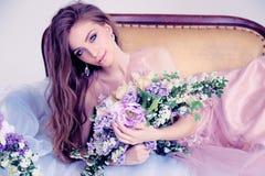 Beautiful woman with long dark hair in elegant dress posing among flowers Royalty Free Stock Images