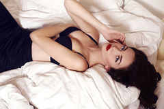 Beautiful woman with long dark hair lying on bed in bedroom Royalty Free Stock Photo