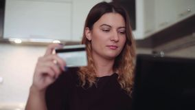 Beautiful women online banking with a credit card having a good mood. Beautiful woman with long dark hair online banking with a computer mouse on the internet stock video footage
