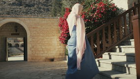 Beautiful woman in long dress and headscarf going upstairs stock video