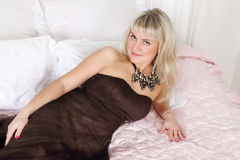 Beautiful woman in long dress lies on bed Stock Photo