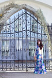 Beautiful woman in long dress posing over old metal gates in old Stock Photography