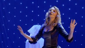 Beautiful woman in long dress sings song on the scene in theatre. Beautiful woman in long dress sing song on colorful stage in the modern theatre. People are stock video