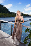 The beautiful woman in a long dress sits on the wooden bridge on the tropical island Stock Image