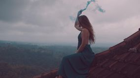 Beautiful woman sitting on the red house rooftop with colored smoke stock footage
