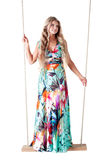 Beautiful woman in a long dress on a swing royalty free stock photos