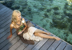 The beautiful woman in a long dress on a wooden platform over the sea Stock Photos