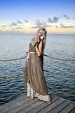 The beautiful woman in a long dress on a wooden platform over the sea Stock Images