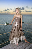 The beautiful woman in a long dress on a wooden platform over the sea Stock Image