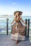 Beautiful woman in a long dress on a wooden platform over the sea Stock Photos