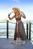Beautiful woman in a long dress on a wooden platform over the sea Stock Image