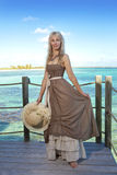 The beautiful woman in a long dress on a wooden platform over the sea Royalty Free Stock Photos