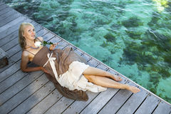 The beautiful woman in a long dress on a wooden platform over the sea Royalty Free Stock Images