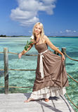Beautiful woman in a long dress on a wooden platform over the sea Royalty Free Stock Photo