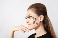 Beautiful woman with long eyelashes and face-art in profile Royalty Free Stock Photography