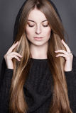 Beautiful woman with long, gorgeous dark blond hair. She is dressed in warm gray knit dress with a hood. Stock Photos