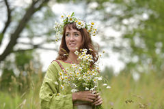 Beautiful woman in a long green dress with flowers Stock Image