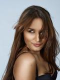 Beautiful woman with long hair. Beautiful brunette hispanic woman with long hair blowing in wind and natural make-up Stock Photo