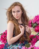 Beautiful Woman with Long Hair on the Background of Peony Flowers Royalty Free Stock Image