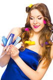 Beautiful woman with long hair in curlers holding products in he Royalty Free Stock Photo